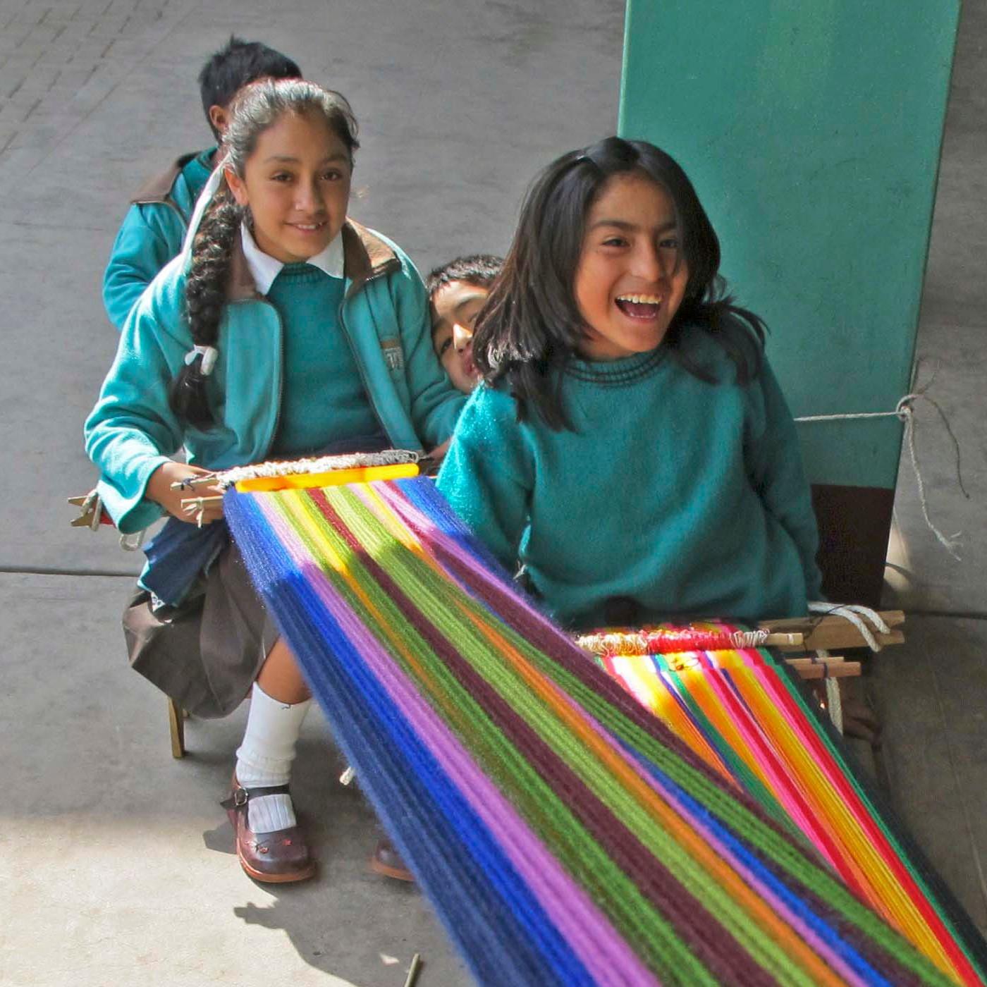 Peruanische Schulkinder beim Weben bunter Stoffe